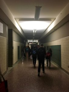 Wilson students walk through mostly-dark hallways after the cancellation was announced. Emergency lights were not affected by the outage and were kept on.