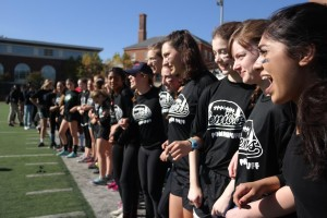 SWEET SIXTEEN– Members of the senior powderpuff team cheer on their teammates from the sidelines. The junior vs. senior powderpuff game is one several time-honored Spirit Week traditions